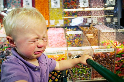 Stock Photo: 1779R-11680 Toddler boy crying in candy aisle of grocery store