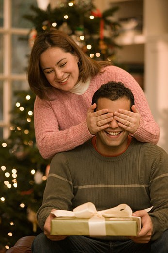 Stock Photo: 1779R-11786 Woman covering husband's eyes from Christmas present