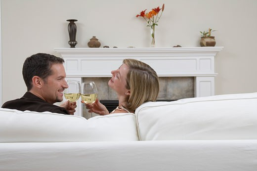 Stock Photo: 1779R-11955 Young couple toasting on couch