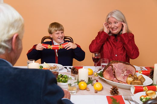 Family opening Christmas crackers : Stock Photo