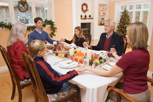 Family saying grace before Christmas dinner : Stock Photo