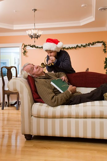 Stock Photo: 1779R-12077 Grandson blowing horn in sleeping grandfather's ear