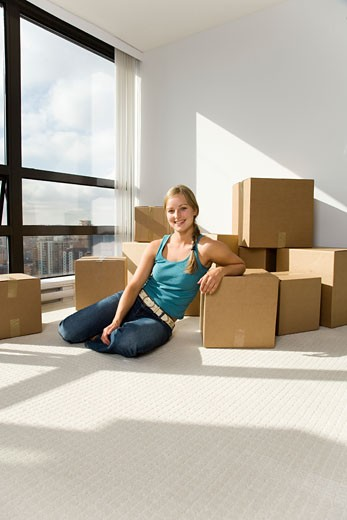 Young woman sitting on floor with boxes : Stock Photo