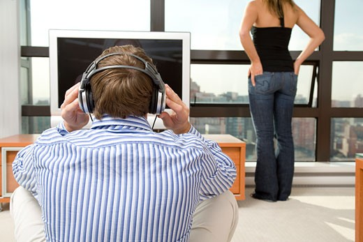 Man listening to music, woman in background : Stock Photo