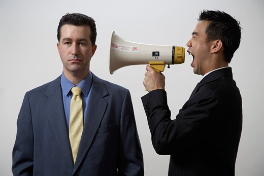 Businessman screaming at co-worker with megaphone : Stock Photo