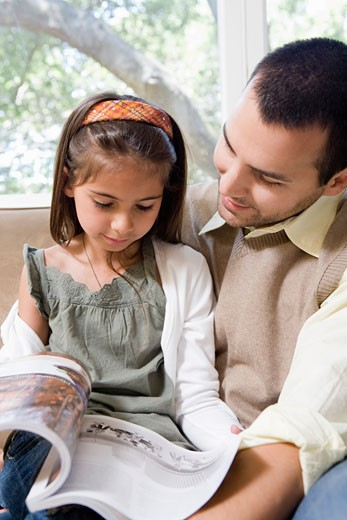 Father and daughter reading on sofa : Stock Photo