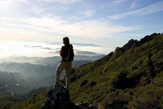 Woman on rock overlooking countryside : Stock Photo