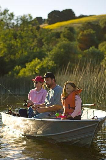 Family fishing in boat on lake in California : Stock Photo