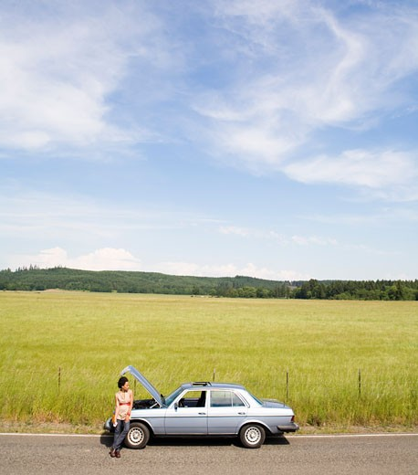 Stock Photo: 1779R-1436 Woman waiting next to broken down car