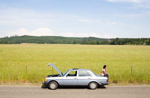 Stock Photo: 1779R-1439 Woman sitting on trunk of broken down car