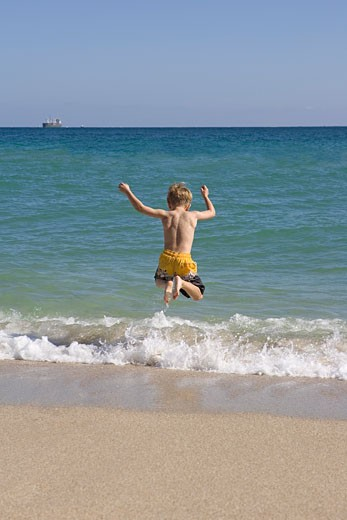Young boy jumping in ocean : Stock Photo