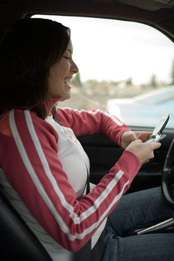 Woman using her cell phone in car : Stock Photo