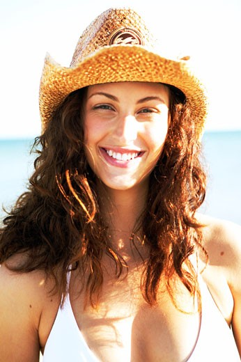 Stock Photo: 1779R-14811 Smiling young Hispanic woman in cowboy hat