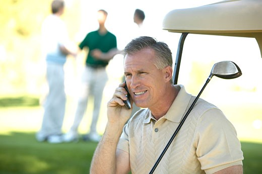 Man talking on cell phone at golf course : Stock Photo