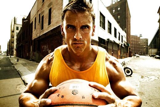 Young man playing basketball on urban street : Stock Photo