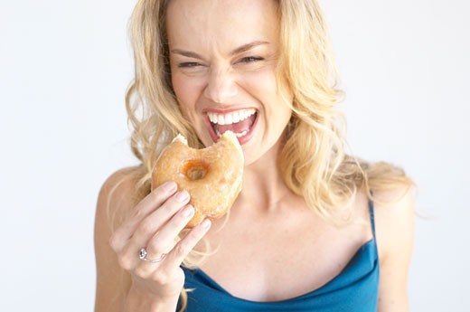 Woman eating a donut : Stock Photo