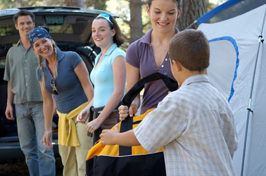 Stock Photo: 1779R-15766 Family passing bags to each other at campsite