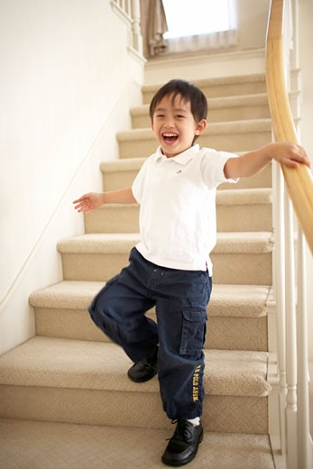 Young boy smiling on stairs : Stock Photo