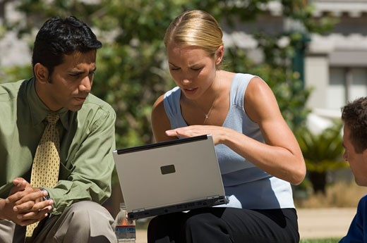 Businesspeople using a laptop outdoors : Stock Photo