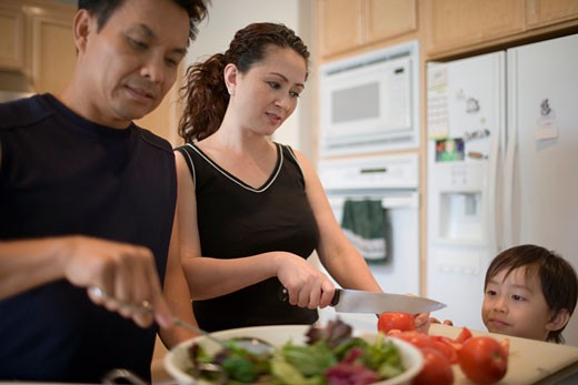 Stock Photo: 1779R-16211 Couple cooking in kitchen