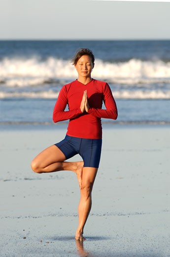 Asian woman in yoga pose on beach : Stock Photo