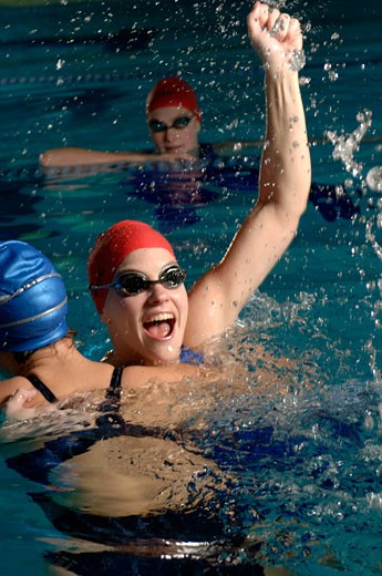 Swimmers celebrating success in swimming pool : Stock Photo