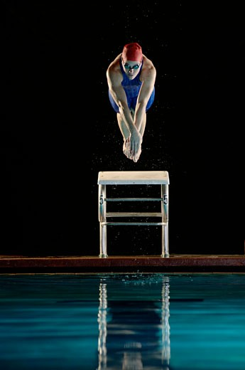 Female swimmer diving off starting block mid-air : Stock Photo