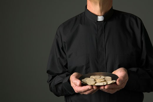 Stock Photo: 1779R-17556 Priest holding bowl of communion wafers
