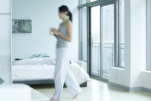 Young adult woman walking in bedroom : Stock Photo