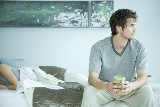 Young adult man sitting on bed near woman : Stock Photo