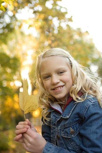 Stock Photo: 1779R-1795 Girl outdoors holding autumn leaf
