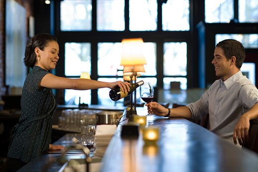 Stock Photo: 1779R-17950 Female bartender with customer at bar