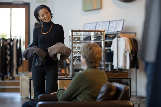 Saleswoman showing man clothing : Stock Photo
