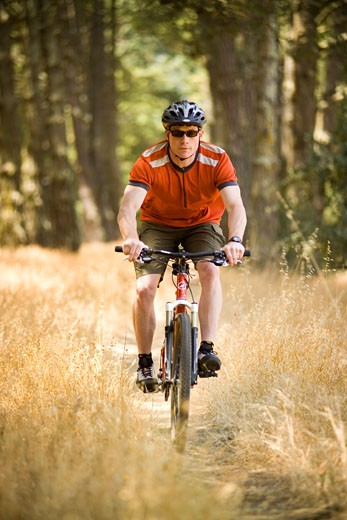Stock Photo: 1779R-18041 Man riding bicycle in woods