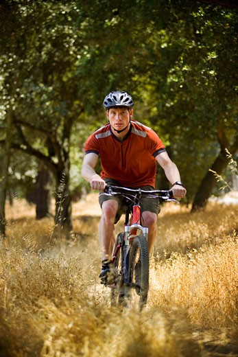 Stock Photo: 1779R-18042 Man riding bicycle in woods
