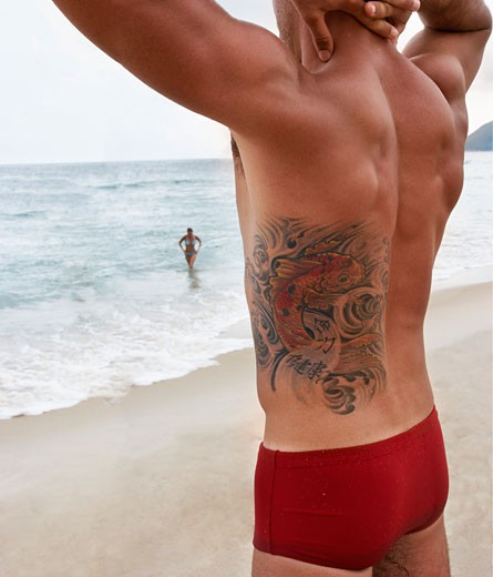 Young man with tattoo on beach : Stock Photo