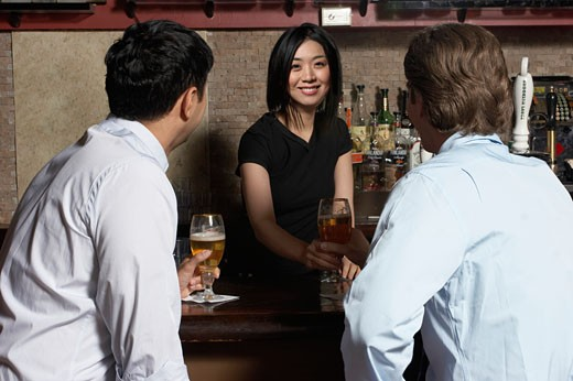 Stock Photo: 1779R-18231 Asian female bartender serving two men at bar