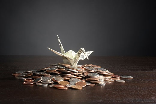 Stock Photo: 1779R-18275 Origami bird with stack of coins