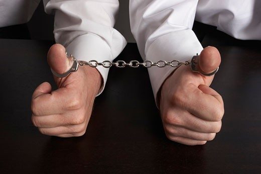 Two businessmen with thumbs handcuffed together : Stock Photo