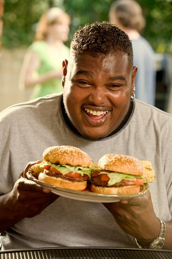African man eating two hamburgers : Stock Photo