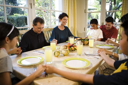 Multi-generation family saying prayer at dinner table : Stock Photo