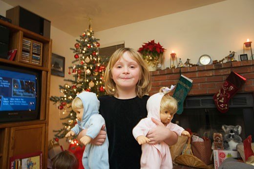 Young girl holding twin baby dolls : Stock Photo