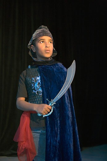 African boy in knight costume on stage : Stock Photo