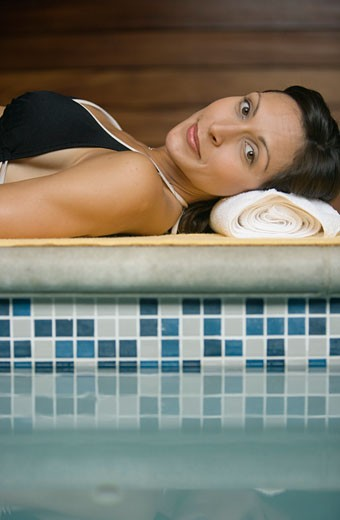 Stock Photo: 1779R-20007 Woman laying by swimming pool
