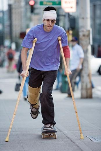 Man on crutches riding a skateboard : Stock Photo