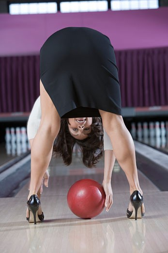 Woman in high heels bending over picking up a bowling ball : Stock Photo