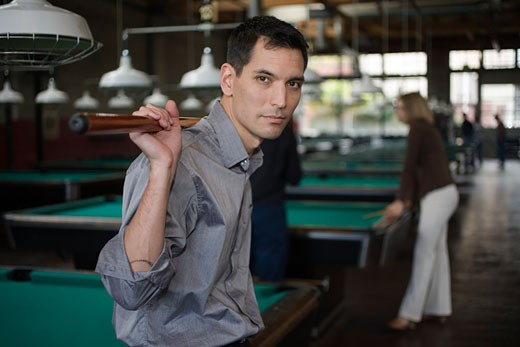 Man with pool cue in pool hall : Stock Photo