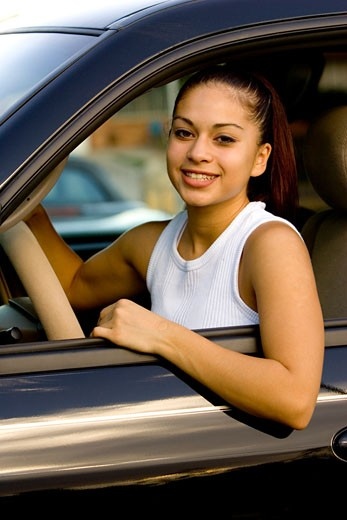 Young woman sitting in driver's seat of car : Stock Photo