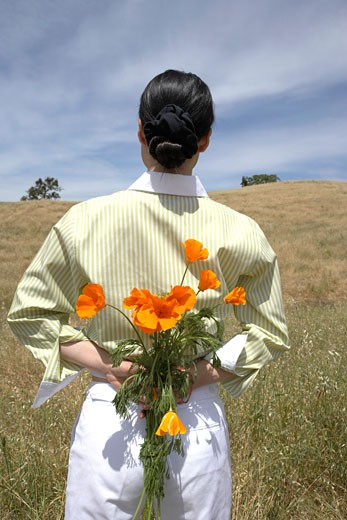 Woman holding bunch of flowers behind her back : Stock Photo