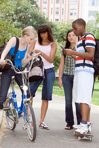 Group of teenagers using hand held devices outdoors : Stock Photo